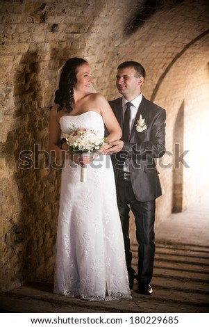 Full length portrait of handsome groom hugging bride at ancient tunnel