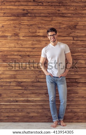 Full length portrait of handsome man in casual clothes and eyeglasses looking at camera and smiling, standing hands in pockets against wooden wall - stock photo