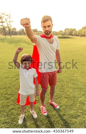 Full length portrait of handsome young dad and his cute little son dressed like superheroes, looking at camera and keeping hand in fist up while playing in park - stock photo