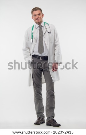 Full length portrait of handsome young doctor in the gauze bandage, standing and putting his hand in his pocket. Isolated on the white background - stock photo