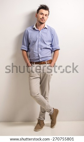 Full length. Portrait of handsome young male on grey background. - stock photo