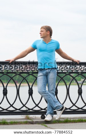 Full length portrait of handsome young man standing outdoors - stock photo