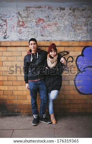 Full length portrait of handsome young man standing with his beautiful girlfriend leaning against a wall. Mixed race teenage couple posing together outdoors - stock photo