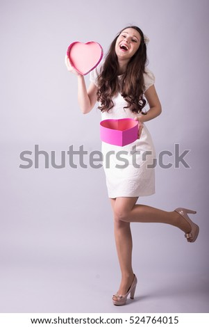 Full length portrait of happy brunette young woman with gift box for Valentines Day. Photo with light background
