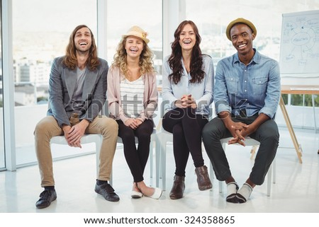 Full length portrait of happy business people sitting on chair in office - stock photo