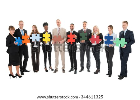Full length portrait of happy business team holding jigsaw pieces against white background - stock photo