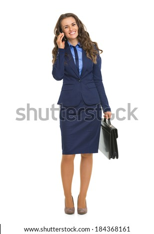 Full length portrait of happy business woman talking mobile phone