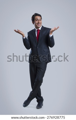 Full length portrait of happy businessman gesturing over gray background - stock photo