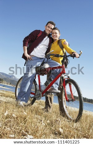 Full length portrait of happy Caucasian couple standing together with a bicycle