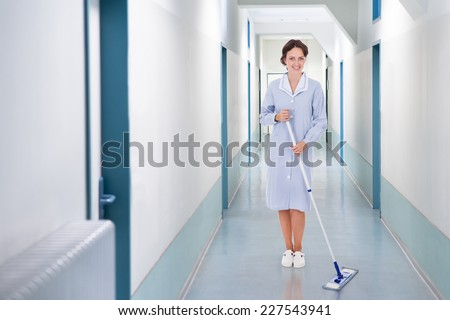 Full length portrait of happy cleaner mopping floor in hospital - stock photo