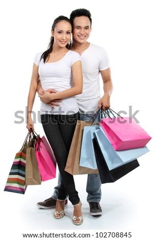 full length portrait of happy couple carrying shopping bag on white background - stock photo