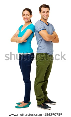 Full length portrait of happy couple standing arms crossed over white background. Vertical shot. - stock photo