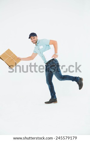 Full length portrait of happy delivery man running with package on white background - stock photo