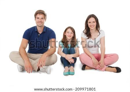 Full length portrait of happy family sitting over white background - stock photo
