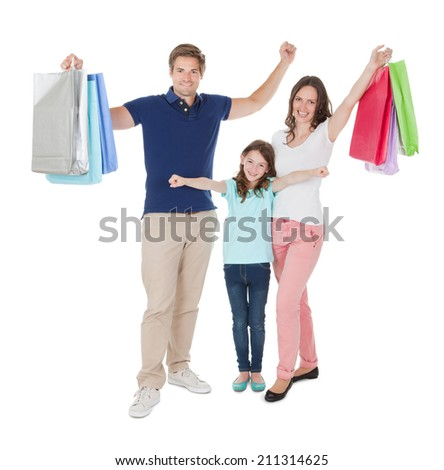 Full length portrait of happy family with shopping bags standing against white background
