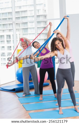 Full length portrait of happy female friends exercising with resistance bands in gym - stock photo