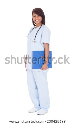 Full length portrait of happy female nurse holding folder while standing against white background - stock photo