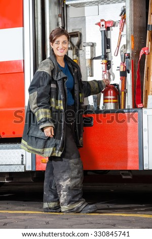 Full length portrait of happy firewoman standing by truck at fire station - stock photo