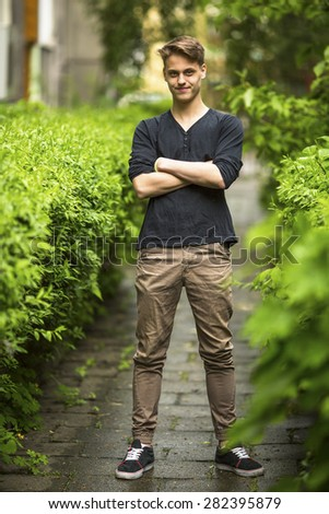 Full length portrait of happy handsome young man summer outdoors.