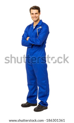 Full length portrait of happy male mechanic in overalls holding wrench over white background. Vertical shot.
