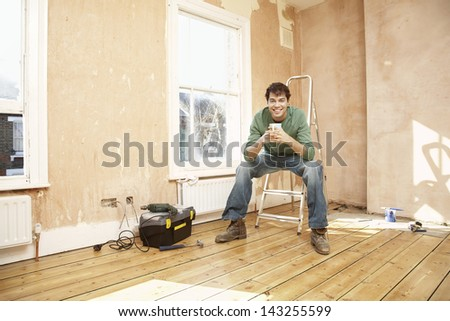 Full length portrait of happy man sitting on step ladder while holding coffee mug in unrenovated room - stock photo