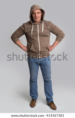 Full length portrait of happy man standing with hand on hips isolated  - stock photo
