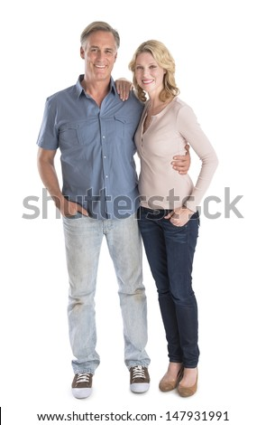 Full length portrait of happy mature couple standing with hands in pockets over white background - stock photo