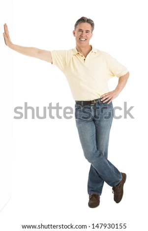 Full length portrait of happy mature man in casuals leaning over white background - stock photo