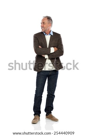 Full length portrait of happy mature man standing with his arms crossed looking away at copyspace on white background - stock photo