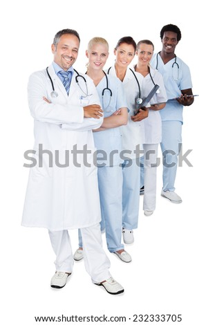 Full length portrait of happy multiethnic medical team standing in row over white background - stock photo