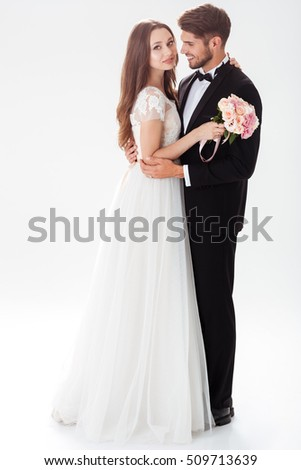 Full-length portrait of happy newlyweds. with bouquet
