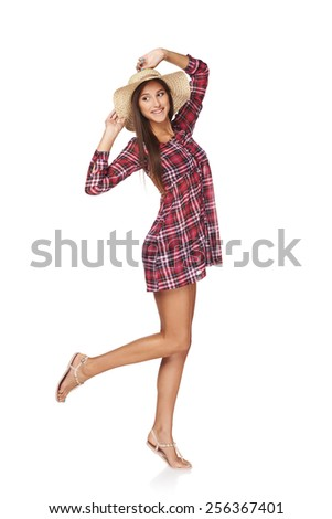 Full length portrait of happy playful woman wearing chequered summer dress and broad-brim straw hat, looking to the side at blank copy space, isolated on white  backgorund. - stock photo
