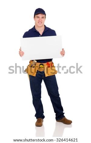 full length portrait of happy repairman holding white board - stock photo