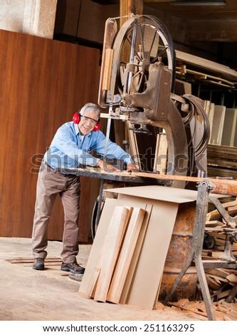 Full length portrait of happy senior male carpenter using bandsaw in workshop - stock photo