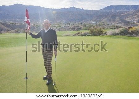 Full length portrait of happy senior male golfer holding flag and putter at golf course - stock photo