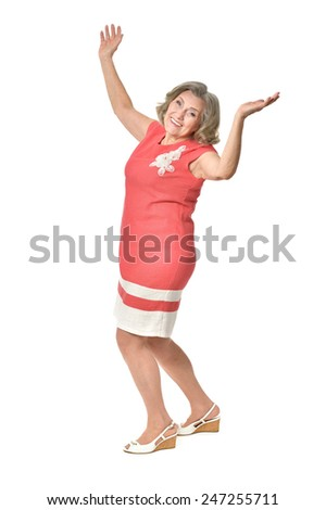 Full length portrait of happy senior woman in red dress with hands upon white background