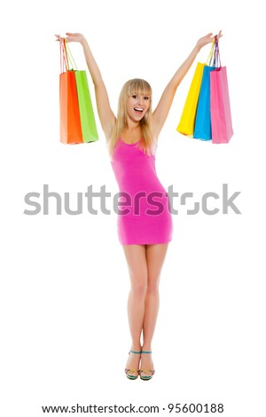 Full length portrait of happy smile beautiful woman hold hands and arms up with colorful shopping bags, girl wear sexy pink short dress, high heels, isolated over white background - stock photo