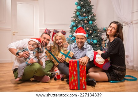 Full-length portrait of happy smiling company of friends sitting on the floor near the Christmas tree showing us their presents celebrating the New Year holiday - stock photo