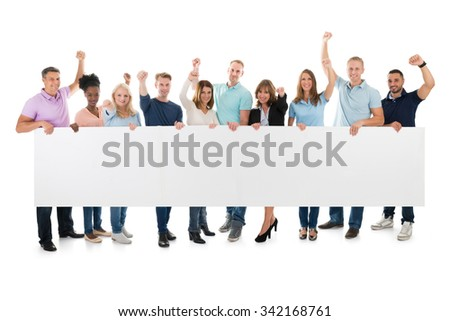 Full length portrait of happy team with arms raised holding blank billboard against white background - stock photo