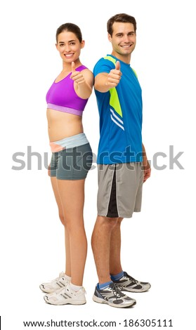 Full length portrait of happy young couple in sports wear gesturing thumbs up over white background. Vertical shot. - stock photo