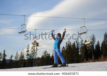Full length portrait of happy young female skier on a sunny day at ski resort against ski-lift. Girl is standing on a ski slope with raised arms as sign of success. Winter vacation. - stock photo