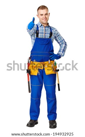 Full length portrait of happy young male construction worker with tool belt showing thumbs up gesture isolated on white background - stock photo