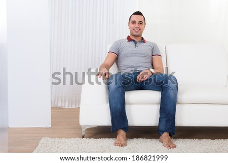 Full length portrait of happy young man sitting on sofa at home - stock photo