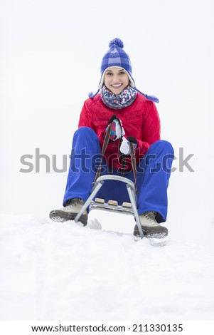 Full length portrait of happy young woman enjoying sled ride in snow - stock photo