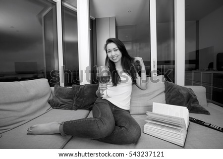 Full length portrait of happy young woman having red wine in living room