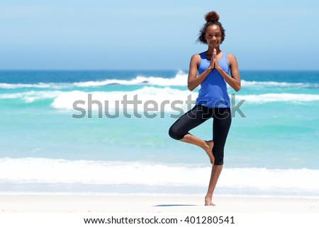 Full length portrait of healthy young woman doing yoga balance exercise at the beach - stock photo