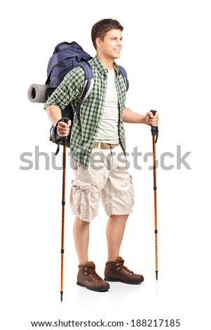 Full length portrait of hiker with backpack holding hiking poles and posing isolated on white background - stock photo