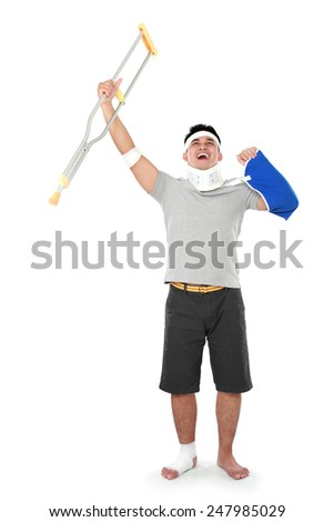 full length portrait of injured young man hold up his crutch - stock photo