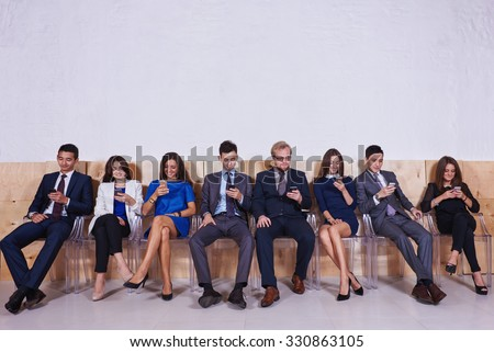 Full length portrait of International group of young intelligent lawyers chatting on they mobile phones, confident business people dressed in office clothing using cell telephones before start meeting - stock photo