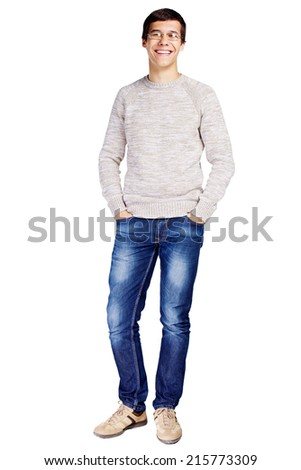 Full length portrait of laughing young man in glasses and beige sweater with hands in his jeans pockets isolated on white background